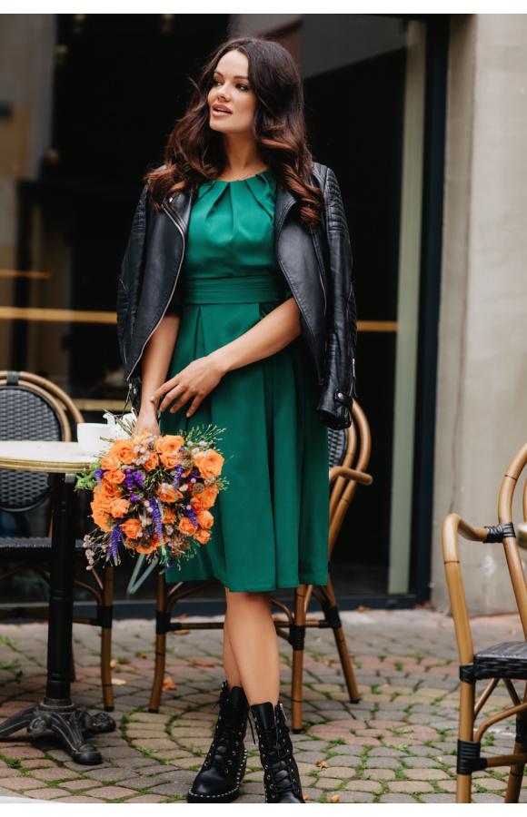 Sukienka w kolorze butelkowej zieleni z odcięciem w talii. Ma piękne marszczenie przy dekolcie.