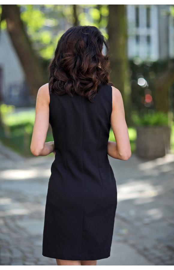 Dwa potrójne rzędy guzików sprawiają, że sukienka nabiera oryginalnego, służbowego charakteru.