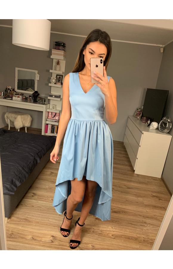 Sukienka ma dłuższy tył i krótki przód, który zachwycająco eksponuje nogi.