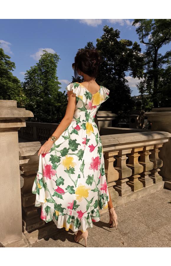 Sukienka na grubych ramiączkach. Przy ramiączkach i dekolcie znajdują się ozdobne falbanki.