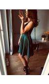 Koktajlowa sukienka w odcieniu butelkowej zieleni. Zachwyca prostym, choć oryginalnym krojem.