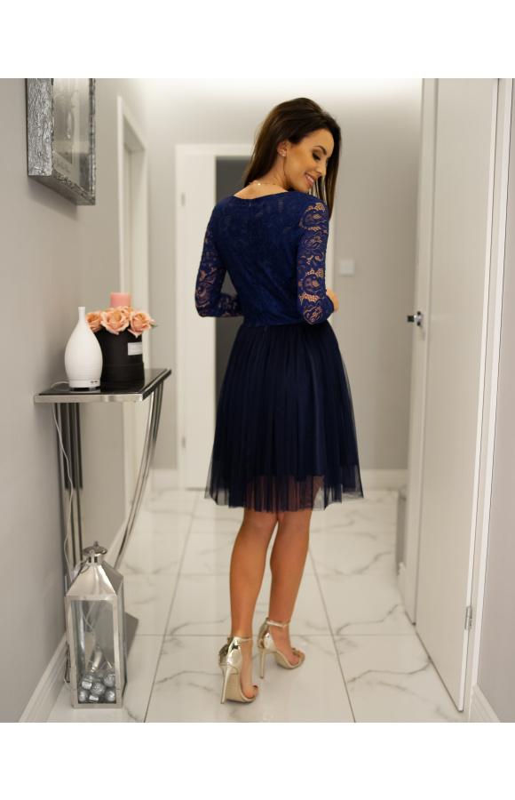 Sukienka ma koronkową górę i tiulową spódnicę, pod którą znajduje się satynowa podszewka.