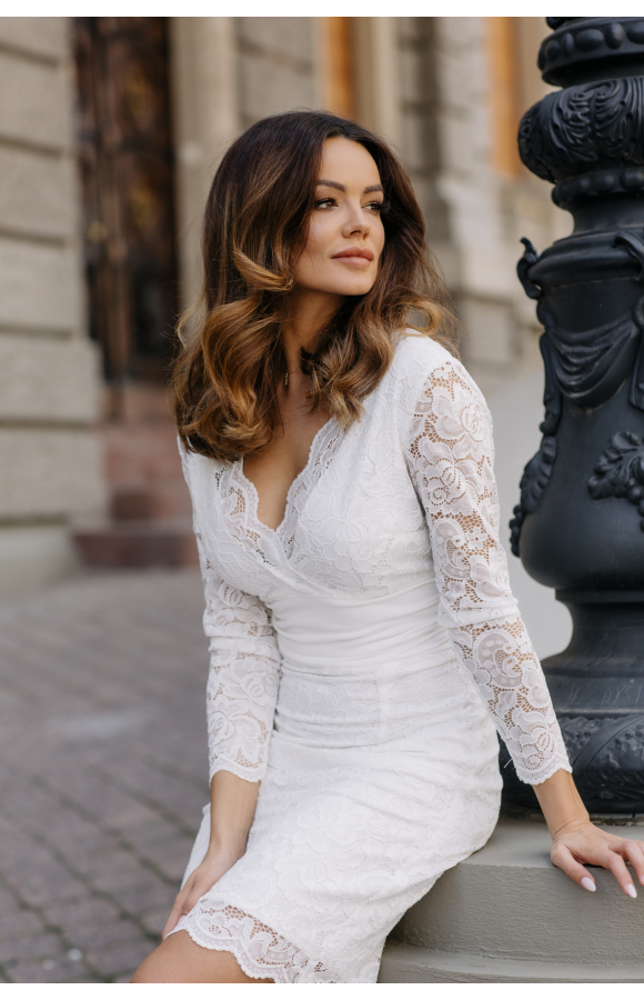 Niezwykle elegancka, dopasowana mini sukienka z długim rękawem. Wykonana z kremowej koronki.