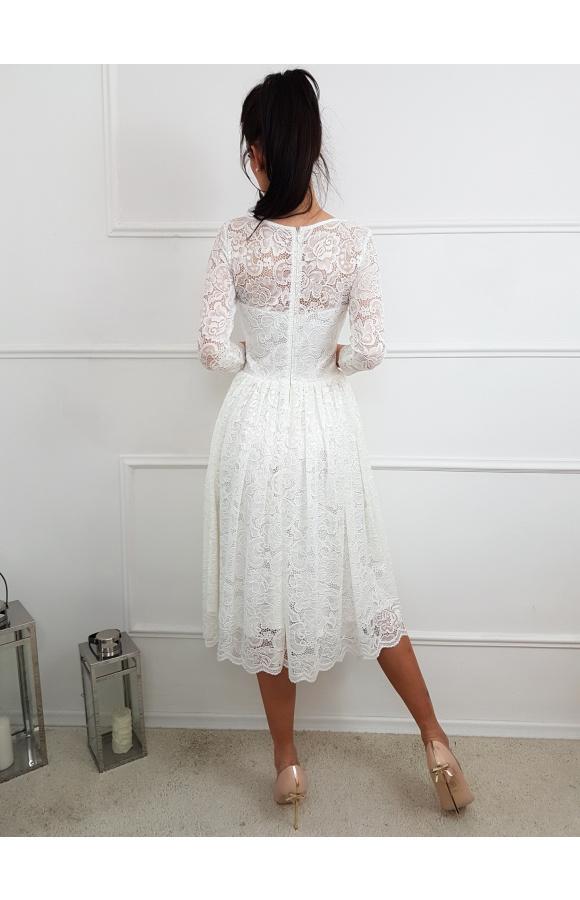 Skromny, prosty fason i imponujące wykończenia przyciągają wzrok i czynią sukienkę wyjątkową.