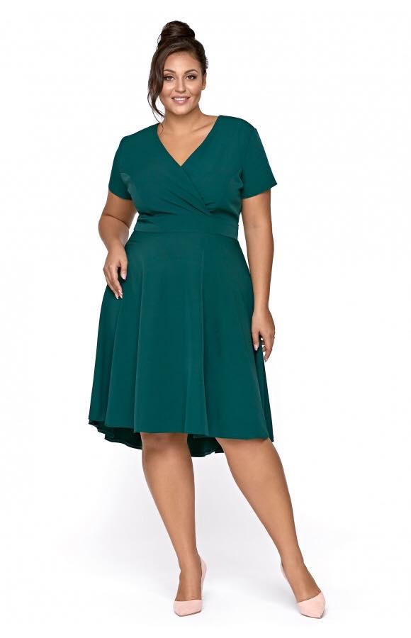 Asymetryczna sukienka midi w kolorze butelkowej zieleni jest idealna na okazje formalne i prywatne.