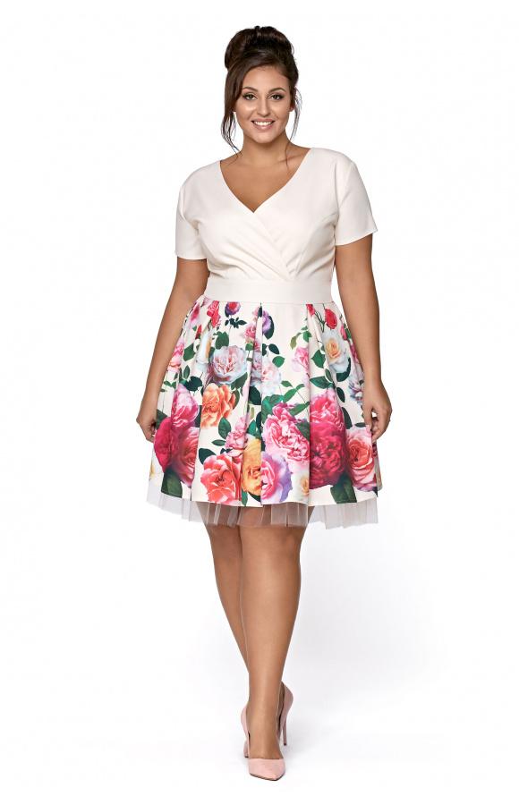 Pokryta wzorem w kwiaty spódnica jest odcinana w pasie, co podkreśla kobiecą sylwetkę.