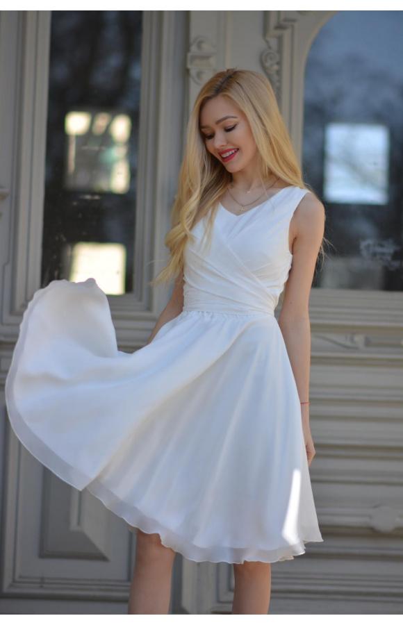 Kremowa sukienka z szyfonu. Fason bez rękawów. Długość do kolana.