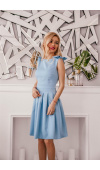 Błękitna sukienka ma ozdobne kokardki na ramionach, co dodaje jej dziewczęcego uroku.