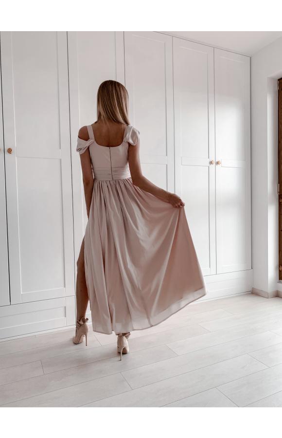 Sukienka jest odcięta w talii szerokim, marszczonym pasem.