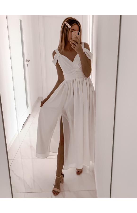 Długa, biała sukienka z odcinanym dołem. Lekko rozkloszowana spódnica ma rozcięcie na nodze.