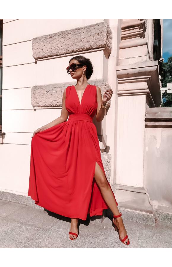 Czerwona sukienka z głębokim rozcięciem na nodze. Szeroki pas pięknie podkreśla talię.