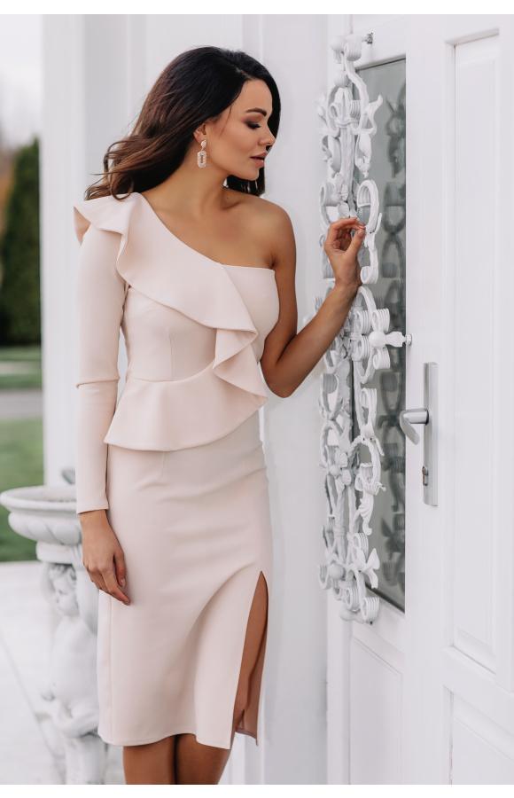Beżowa, asymetryczna sukienka z jednym rękawem. Krój midi i rozcięcie na udzie podkreślają sylwetkę.