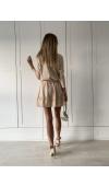 Beżowa sukienka mini z długim rękawem, którą ozdobiono falbanami w dole spódnicy i na rękawach.