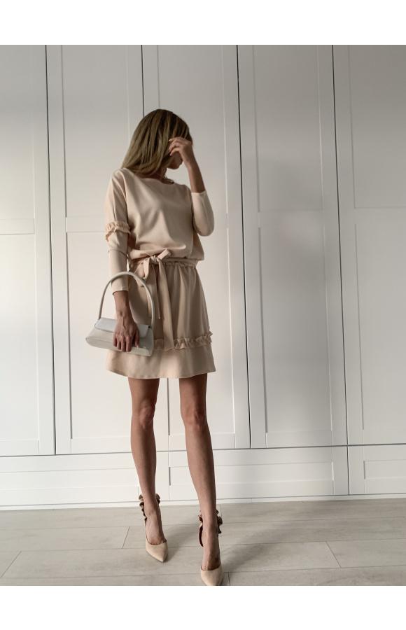 Beżowa sukienka oversize z długim rękawem. Z ozdobnymi falbanami na spódnicy i rękawach.