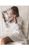 Urocza, biała sukienka oversize o kroju midi i z długim rękawem. Ozdobiona falbanami i paskiem.