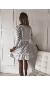 Oversizowa sukienka w kolorze białym. Krój midi, długi rękaw, ozdobne falbany w dole i na rękawach.