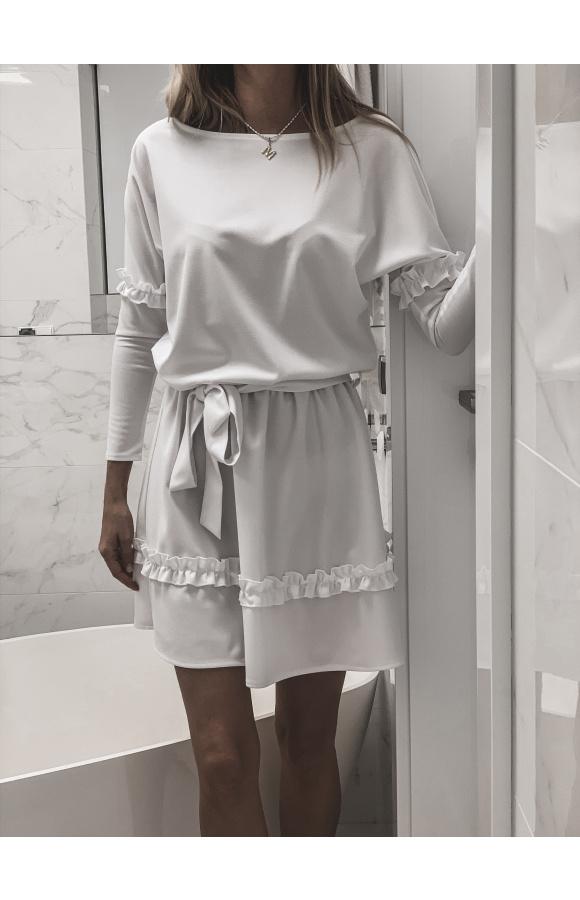 Biała, dzianinowa sukienka oversize z długim rękawem. Ma ozdobne falbanki na rękawach i spódnicy.
