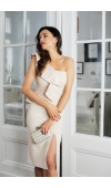 Dopasowana, beżowa sukienka o asymetrycznym kroju i z odsłoniętym ramieniem.