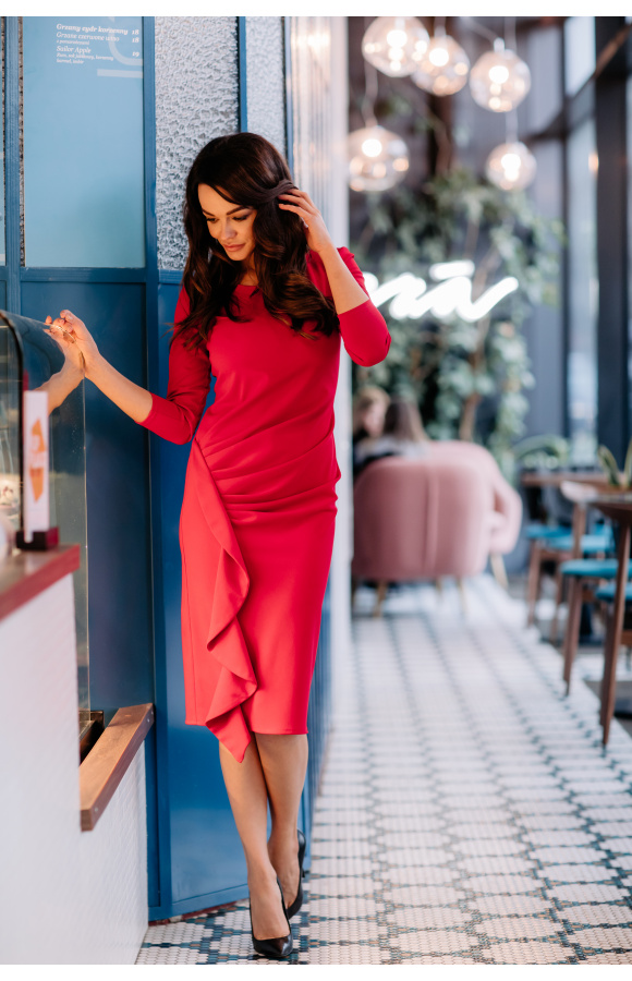 Piękna, czerwona sukienka o prostym, dopasowanym kroju. Ma drapowanie w pasie i boczną falbanę.