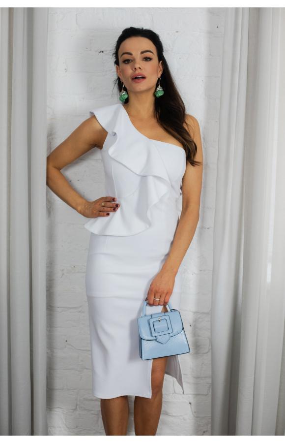 Elegancka, biała sukienka midi z ozdobną falbaną. Jedno ramię odkryte, a na udzie jest rozcięcie.