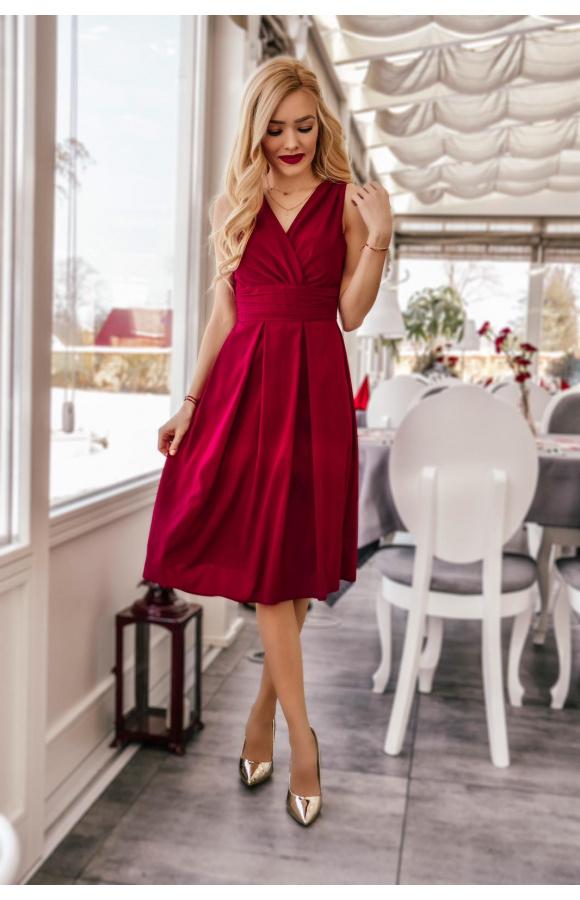 Sukienka midi bez rękawów z głębokim dekoltem w kształcie V i rozkloszowaną spódnicą.