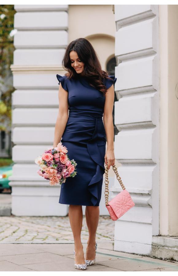 Sukienka ma ozdobne falbanki zamiast rękawów. Pionowa falbana zdobi też dół spódnicy.